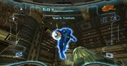 View of a futuristic looking room; an enemy in a big, futuristic-looking black powered suit with a helmet, large, bulky, and rounded shoulders charges the firearm on the right arm. The player's weapon (a large cannon) is visible in the corner of the screen. The image is a simulation of the heads-up display of a combat suit's helmet, with a crosshair surrounding the enemy and two-dimensional icons relaying game information around the edge of the frame.