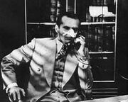 Black-and-white image of a man with a heavily bandaged nose sitting and talking on the phone. He wears a cream-colored suit and vest and boldly patterned tie; the collar of a white shirt is visible. Behind of him is a bookcase; in front of him, the edge of desk. A series of diagonal shadows descending from upper left falls over most of the image.