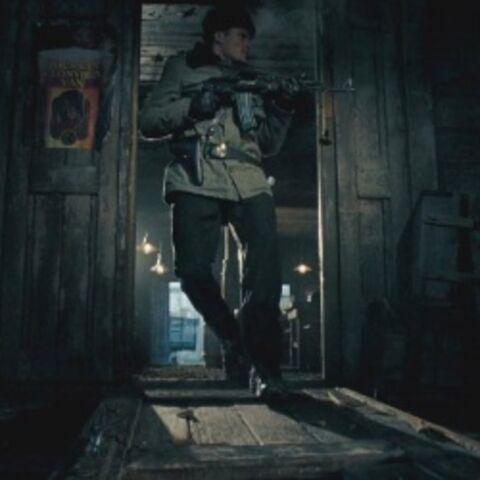 A police officer runs through the tavern door with his weapon ready.