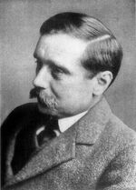 Black-and-white photo of a man with bushy black moustache and black hair with parting.
