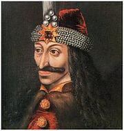 Painting of a richly dressed Caucasian man's head and shoulders. He has long, curly black hair and a moustache. He is wearing a red hat with a wide band of pearls and a gold star and red gemstone on the front. He is wearing a brown fur cape, over a red and gold top.