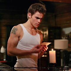 Stefan looking at a photo of Katherine which Elena saw before-hand and left her vervain necklace next to it.