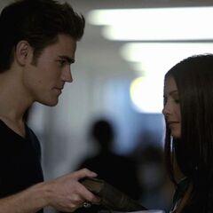 Stefan gibt Elena ein Buch.