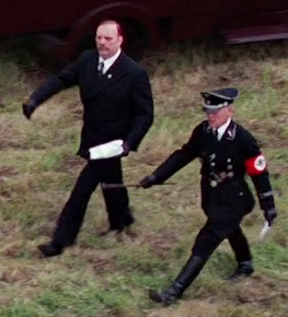 The enraged Standartenführer marches in goose step with his Gestapo lover