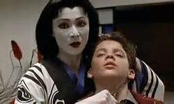 Lady Tanaka hold a hidden knife next to Tommy's neck