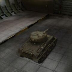 A rear right view of a M4A3E8 Sherman in a garage
