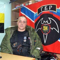 Командир ГБР Беднов на фоне боевого флага Новороссии с эмблемой своего подразделения.