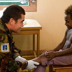Новозеландский врач обследует мальчика, который живет на Соломоновых островах.
