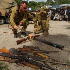 Члены RAMSI уничтожают отобранное у преступников оружие.