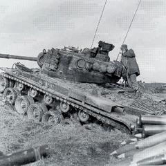 M46 1-го танкового батальона морской пехоты, ожидающий указаний на огневой позиции. На переднем плане — сложенный рядом с танком дополнительный запас осколочно-фугасных выстрелов для продолжительного огня. Корея, декабрь 1952 года.