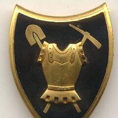Эмблема инженерных частей, напоминающая французскую: кираса на фоне перекрещенных лопаты и кирки.
