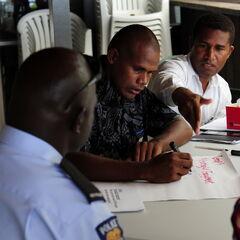 Полицейский получает письменные показания от местных жителей.