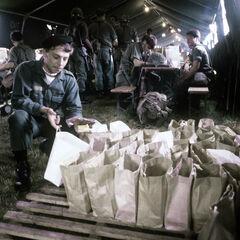 Рядовой люксембургской армии проверяет завтраки для британских солдат, 1980 год.