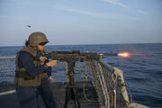 U.S. Navy Ship's Serviceman 3rd Class Hoi Hang Yu fires a M240B machine gun during a live-fire exercise aboard the guided missile destroyer USS Stout (DDG 55) Jan. 4, 2014, in the Mediterranean Sea 140104-N-UD469-