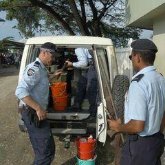 Офицер полиции Соломоновых Островов помогает своим коллегам из Австралии загрузить в машину оружие, отобранное у бандитов.