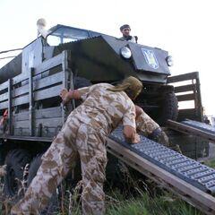 Бойцы выгружают с грузовика свой бронеавтомобиль.
