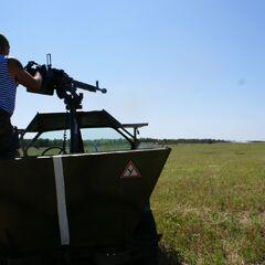 Боец батальона ведет стрельбу из ДШК на техничке