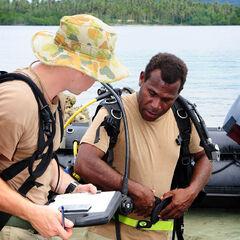 Полицейские RSIPF проверяют свое оборудование перед погружением в воду.
