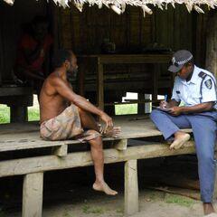 Полицейский собирает показания у местных жителей.