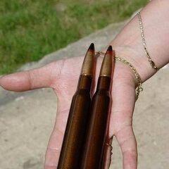 12,7-мм патроны на человеческой ладони.