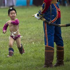 Монгольский мальчик в костюме проходит мимо члена почетного караула на фестивале