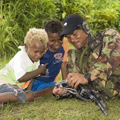 Новозеландский солдат показывает местным детям фотографии на своем фотоаппарате.