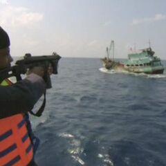 Член патруля стреляет в рулевую трубку судна.