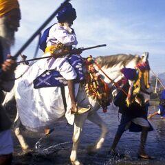 Современный сикх-акали переправляется через реку Чаран Ганга верхом на лошади, 2007 г.