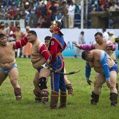 Кавалерист из почетного караула среди монгольских борцов, Улан-Батор, Монголия, 11 июля 2012 года.