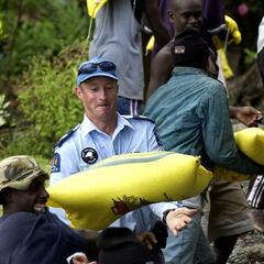 Новозеландский полицейский помогает носить мешки с провизией.