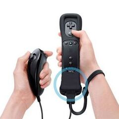 A black Wii Remote with Wii MotionPlus and a <a href=