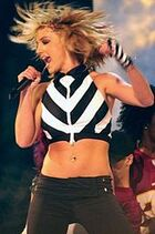 A blonde woman wearing a black and white top and black pants is performing