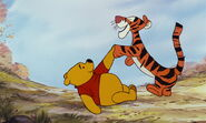 Tigger is shakeing Pooh Bear's paw again