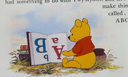 Winnie the Pooh is reading and learning a book about ABC's that's upside down