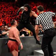 Reigns uses the steel steps as a launchpad to land a Superman Punch