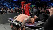 Orton suplexes Nakamura onto the announce table