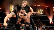 Ambrose and Reigns brutally attacking Langston
