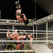 Strong chases Cole to the top of the structure and suplexes Cole onto a plethora of Superstars