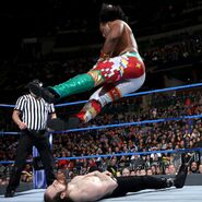 Xavier Woods puts an elbow drop on Aiden English