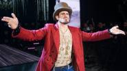 Aiden English entrance wearing a top hat and a jacket