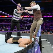 Gallagher traps Itami under the ring apron skirt