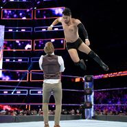 Itami jumps with a clothesline on Gallagher