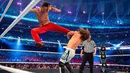 Nakamura jumps with a kicks into AJ Styles