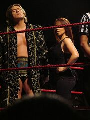 A man and a woman standing in a wrestling ring with red ropes. The man is standing on the left, and has light brown hair. He is wearing a long black coat with gold detailing, short black wrestling tights, and has a wrestling championship around his waist. The woman is standing beside him, but has her face obscured by the ring ropes. She has shoulder length brown hair, and is wearing a black top and black trousers.