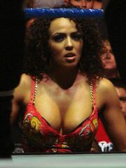 A close-up shot of a tanned, Caucasian female with curly black hair. She is wearing a red top with a yellow and white pattern visible, and a blue rope from a wrestling ring is visible in the foreground.