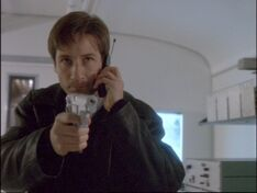 Fox Mulder aims a gun in 1997