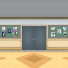 Afiches en la pared al lado de unos trofeos frente a los casilleros.