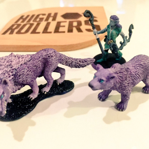 Miniatures of Elora (clockwise from left: dire wolf, Elora, bear), pictured alongside a fan-made High Rollers D&D coaster