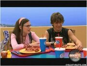 Quinn and Logan sit next to each other at the lunch table.